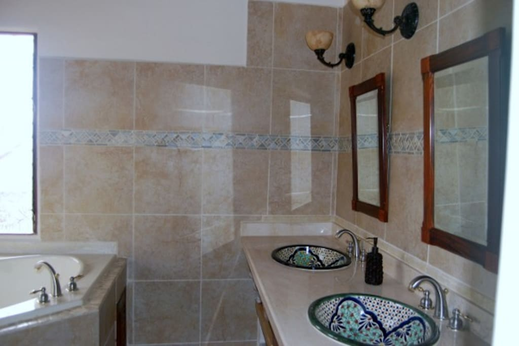 Master bath has twin Talevera sinks ..Travertine tiled walk in shower and large soaking tub