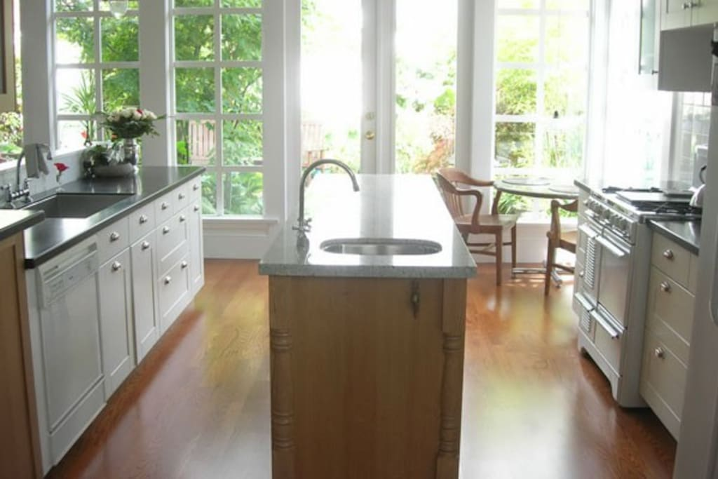 Wonderful sunny kitchen with gas stove, island and two sinks.