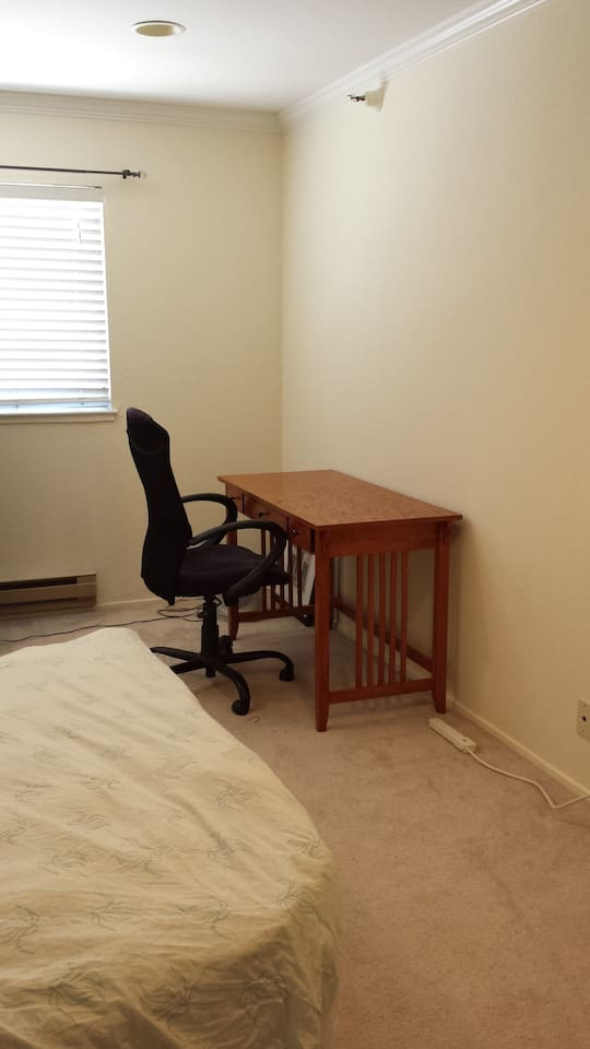 Clean wooden table and computer chair for use. Outlets are located nearby the desk and bed.