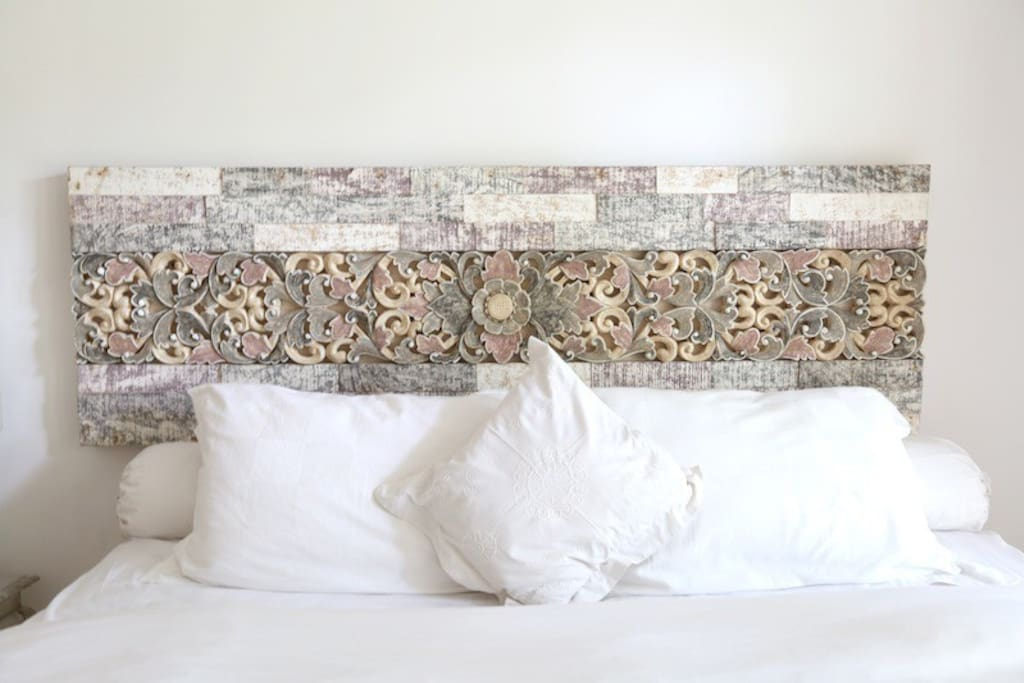 Balinese carved headboard and luxurious linens