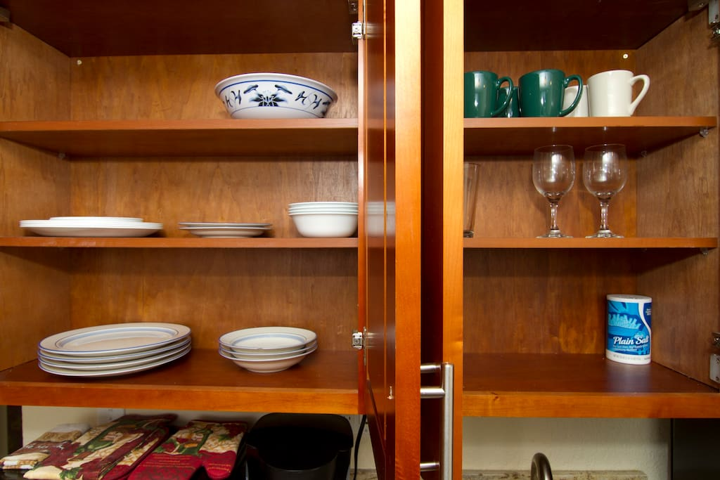 Electric stove stowed in cabinet. Glassware, dishes and utensils.
