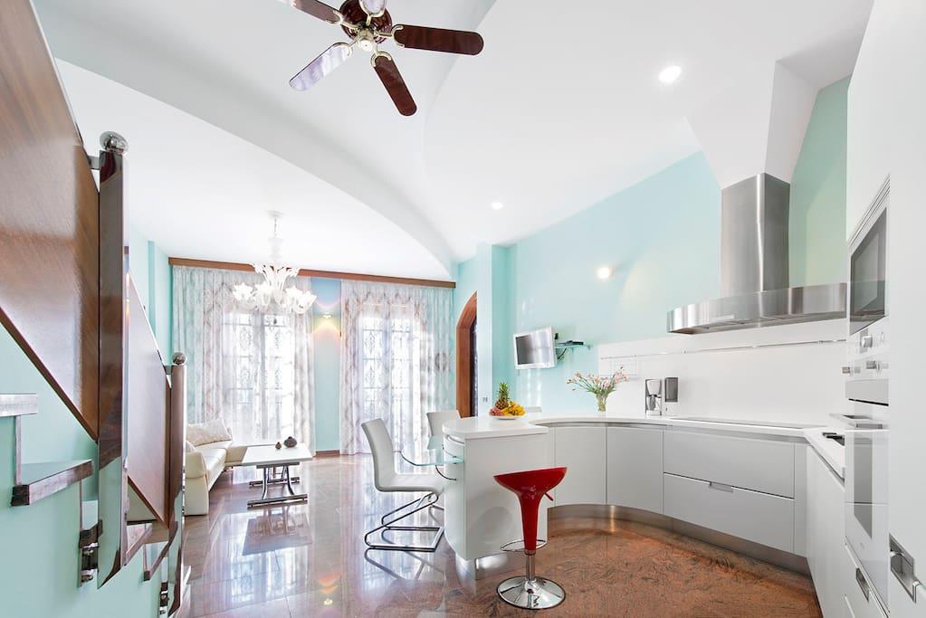 Spacious living room of 45m2, with high ceilings and an open Italian design kitchen. *** Salón amplio de 45 m2 con techos altos con la cocina abierta integrada de diseño italiano.