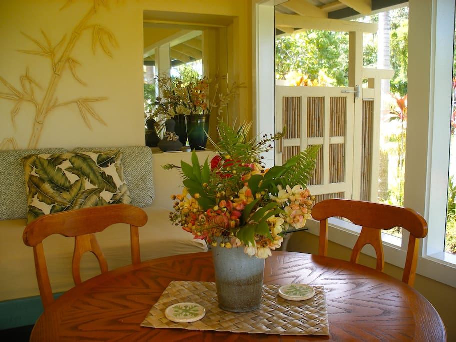 The screened lanai (sunroom) is furnished with a punee (day bed) and dining table
