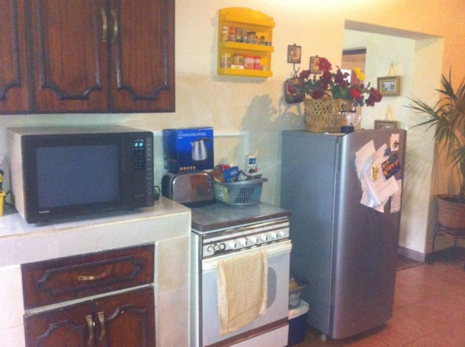 kitchen with microwave, fridge, gas oven and plates