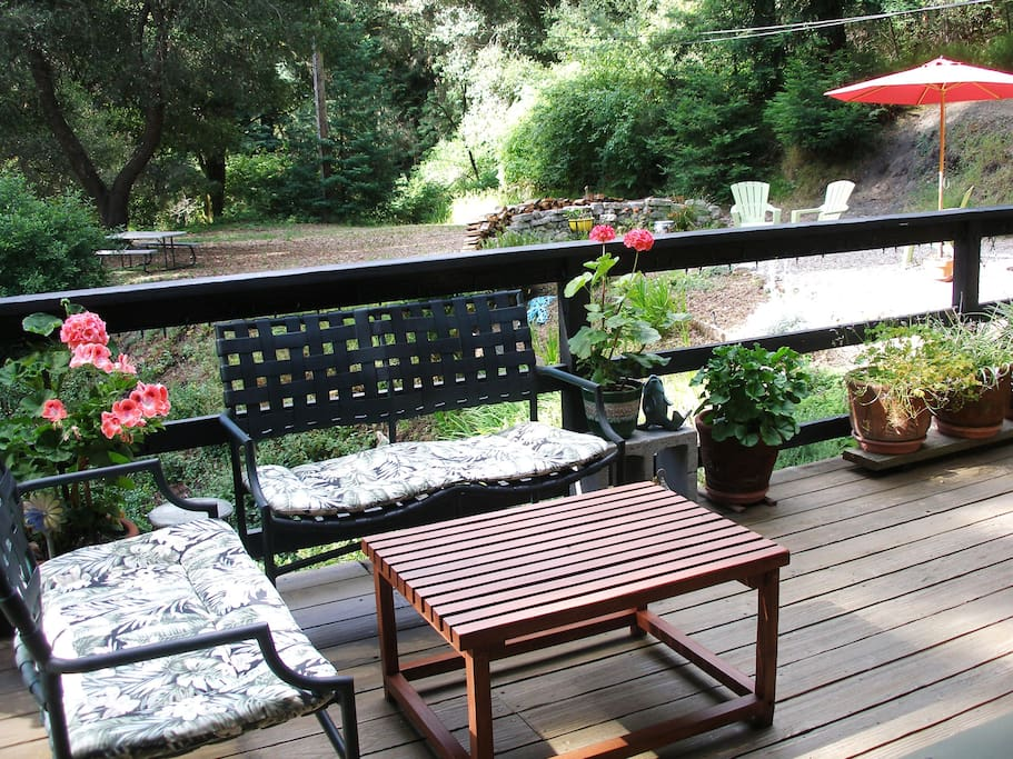 The deck off the living room has seating for conversation and a table with chairs for dinning