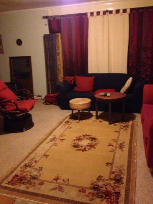 Colourful lounge-room/sitting room. Good-sized TV