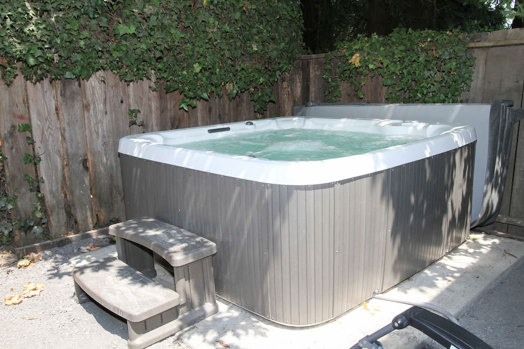 Huge hot tub for 5-6 persons on cement pad & paver patio with zero-gravity chairs
