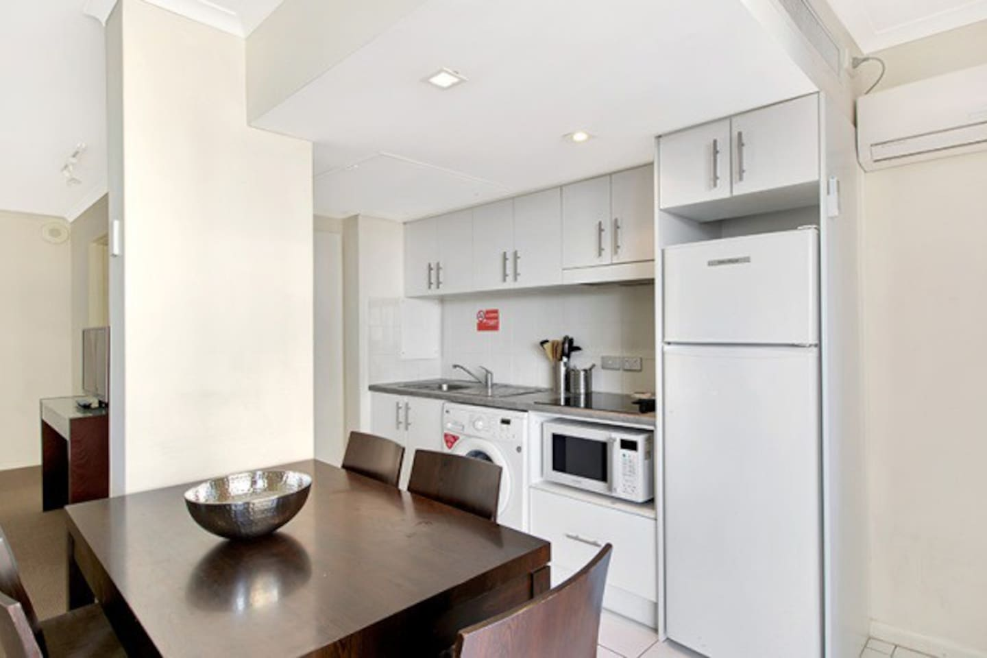 Complete galley kitchen, cook top, microwave oven, washing machine.