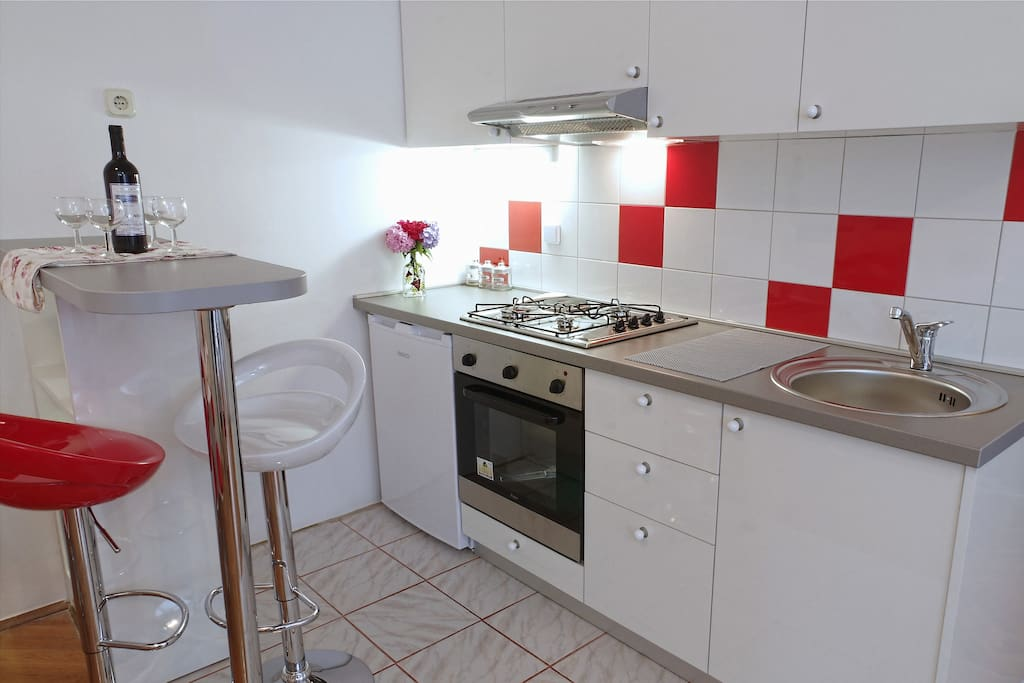Brand new kitchen with cooktop, oven and refrigerator