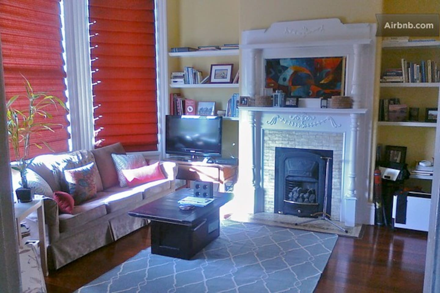 Living room with queen sofabed, HDTV, gas fireplace, crown molding and quaint street views.