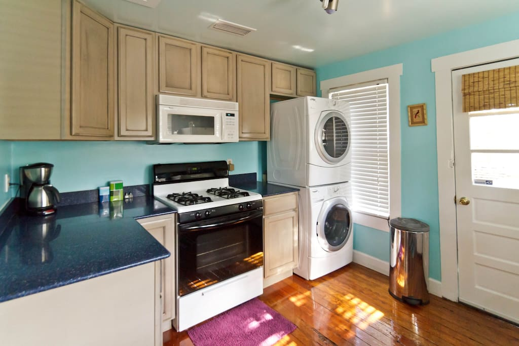 Kitchen with granite counters, gas stove and front loader washer and dryer.