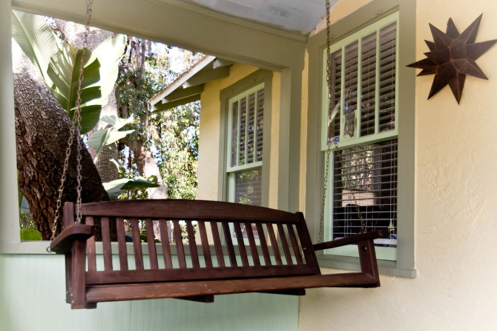 Enjoy the front porch and the old Florida landscaping.