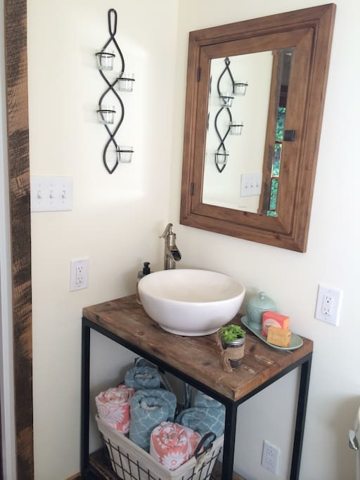 Rustic vanity with vessel sink and medicine cabinet to store your toiletries.