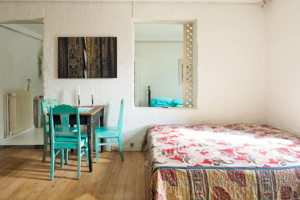 Oppholdsrom med spiseplass og dobbeltseng.