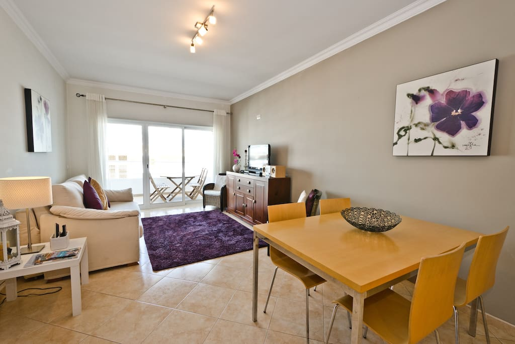 Nicely decorated living/dining room leading to spacious balcony with barbecue
