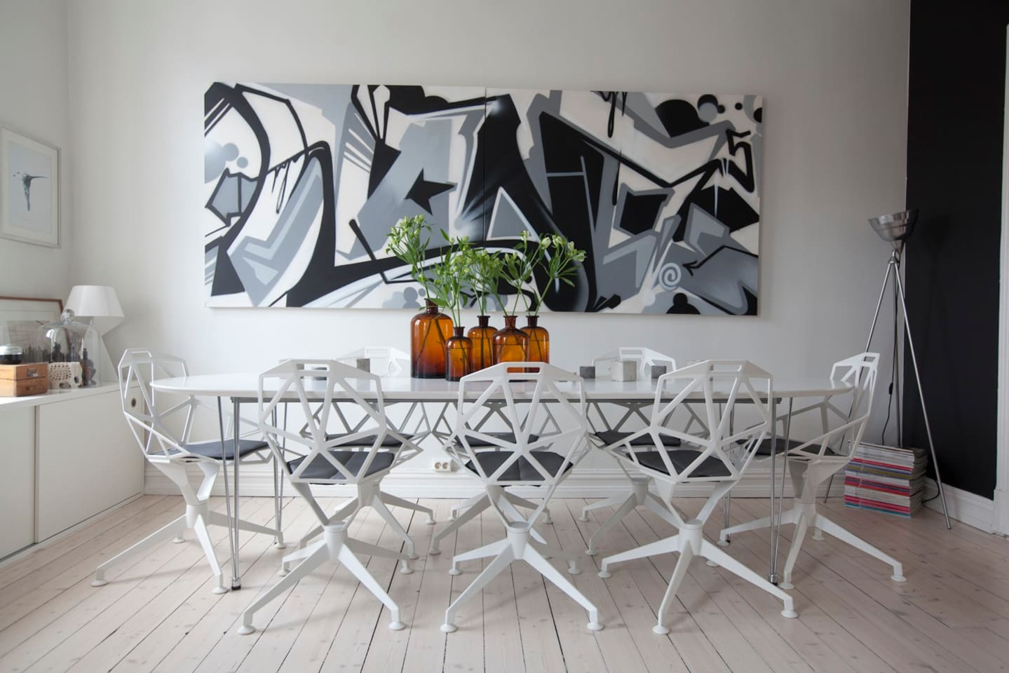 Dinning area with design chairs Chair one from Magis. Big graffiti picture in the back is from a NY artist called Wane COD