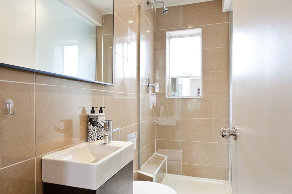 Bathroom tiled, with mirrors with walk-in shower, and window for natural ventilation