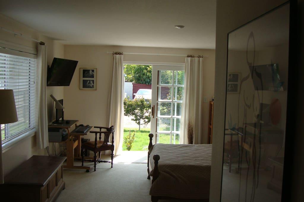 Master bedroom with Tv and Queen size bed. Sliding door to backyard