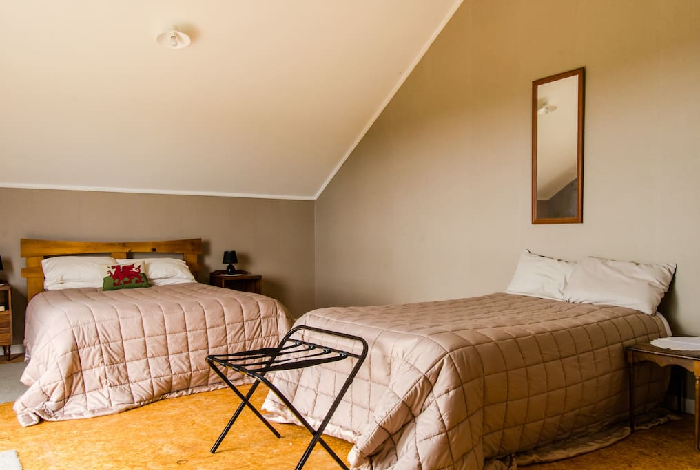 Bedroom 1 - with Queen and single bed. Has a deck that looks out across farmland to the sea.