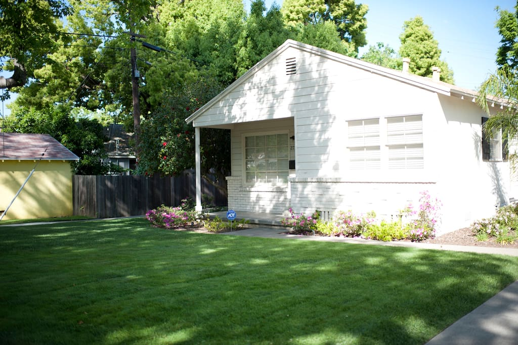 Well manicured front lawn with seasonal blossoms and a large shade tree.