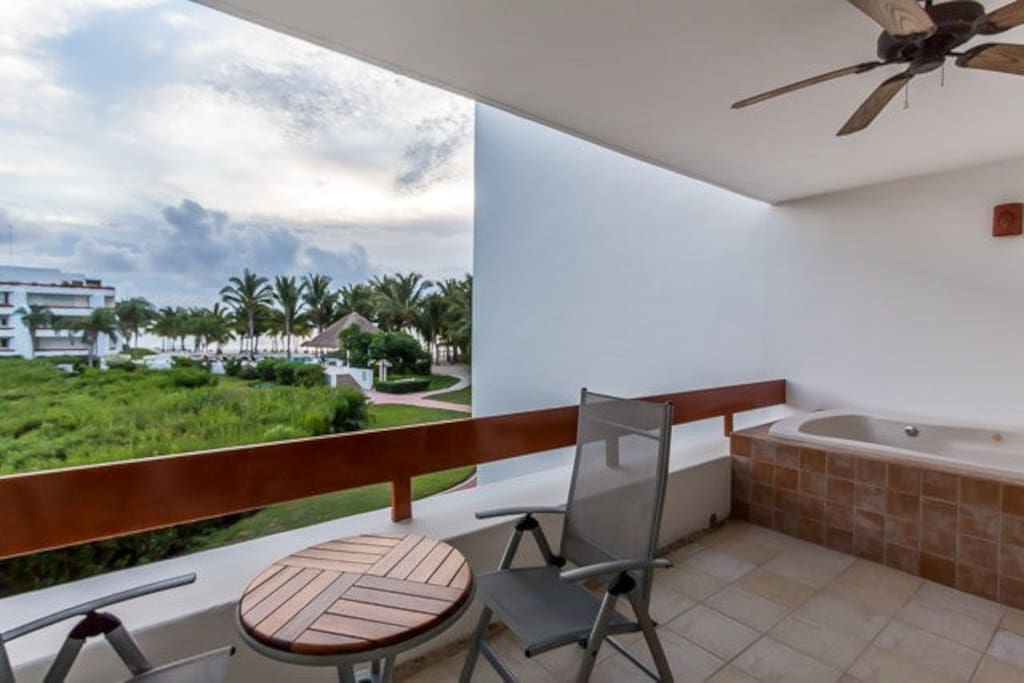 The balcony has ocean views, a small table for watching the sunset, and a Jacuzzi tub
