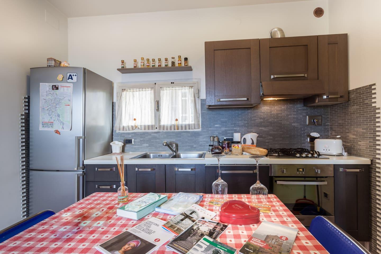 Cucina con frigosurgelatore, lavastoviglie, angolo cottura e forno ventilato.