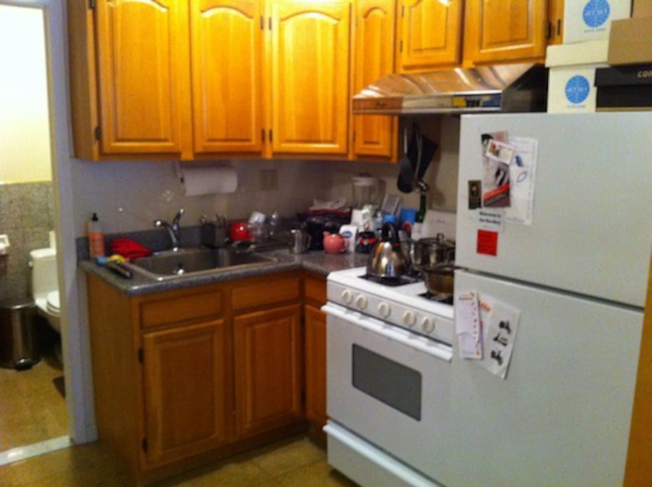Kitchen with all main dining and cooking needs: Cutlery, flatwear, bowls, dishes, cups, glasses, coffee grinder, French press coffee maker, pots, pans, fridge, stove, etc.
