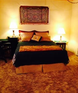 This spacious bedroom (in the open loft of an adobe home/Yoga studio-located in the quaint Village of Corrales NM) has a queen size bed, daybed, dresser, side tables & desk w/lamps. The bathroom & living/dining area is shared w/other guests. Sleeps 1-3 people.