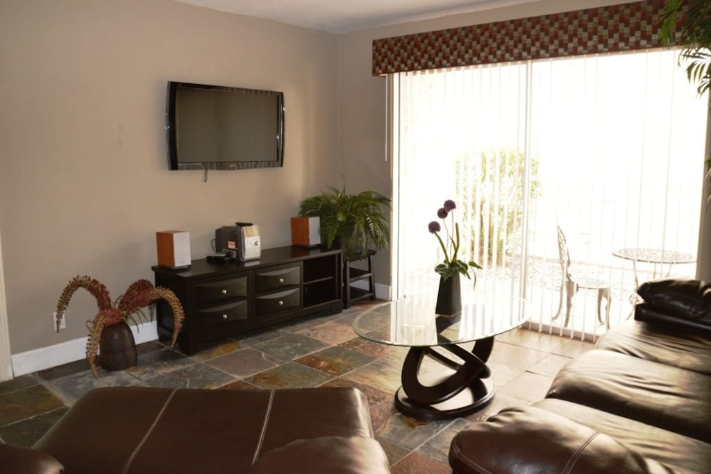 Awesome living room with leather chair and sofa, plasma screen TV and patio off the room