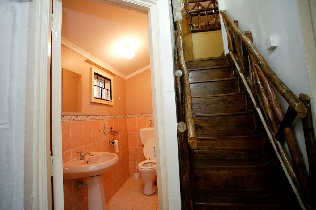 Cottage living room toilet next to loft staircase