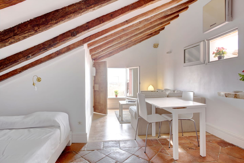 La zona de estar: el amplio sofá en L orientado hacia la ventana y una mesa con dos confortables sillas para comer o trabajar.