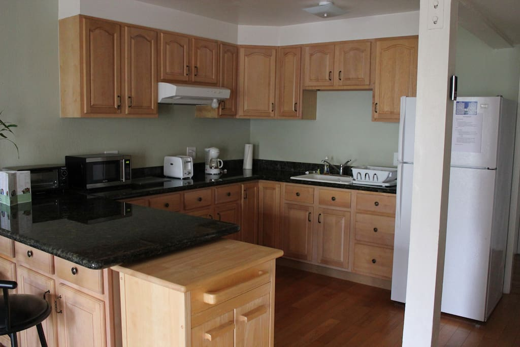 Kitchen is equipped with refrigerator, microwave, toaster oven, toaster, and coffee pot