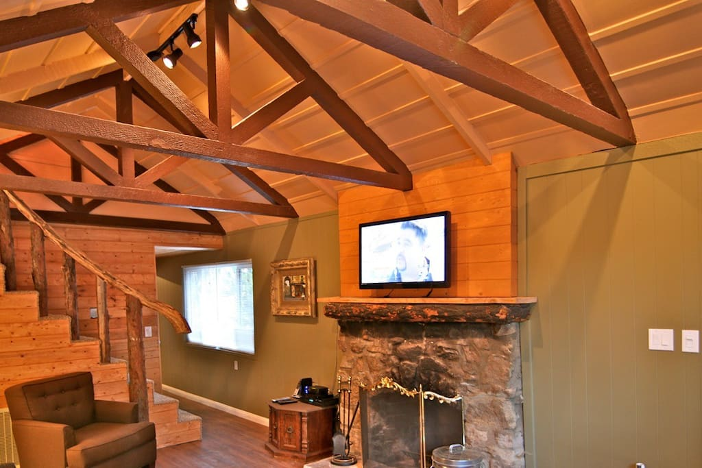 Flat screen TV above the fireplace mantle. Vaulted ceilings with exposed beams