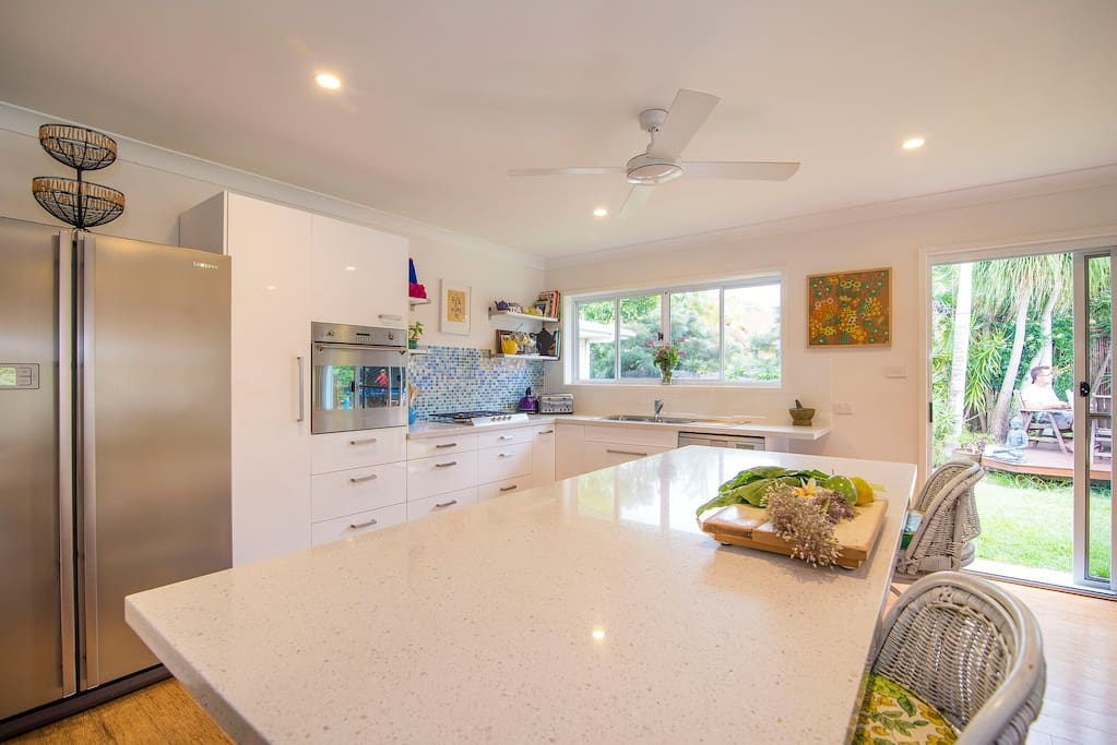 Huge, gourmet kitchen, with giant island bench and high end stainless steel appliances.