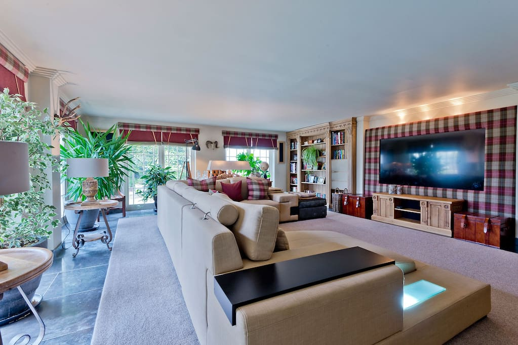 Main lounge with huge flush TV screen and home entertainment centre