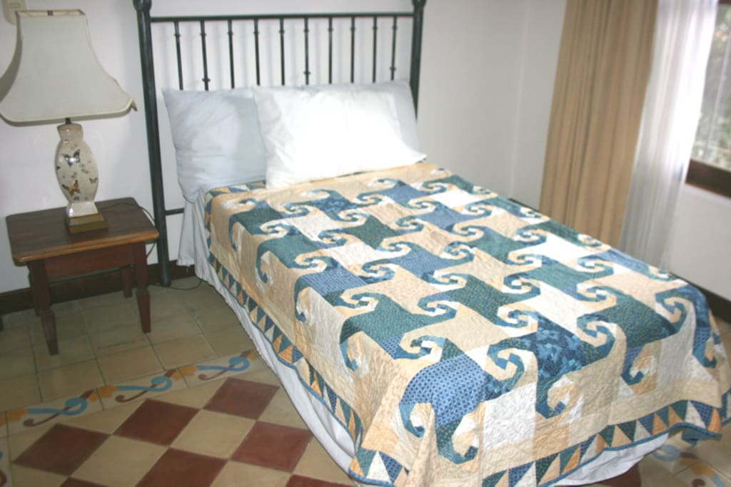 Twin-sized bed with one bedside table and lamp. We can put a normal reading lamp instead of that one. There's also a bigger bed and a bunk bed available instead of the one you see.