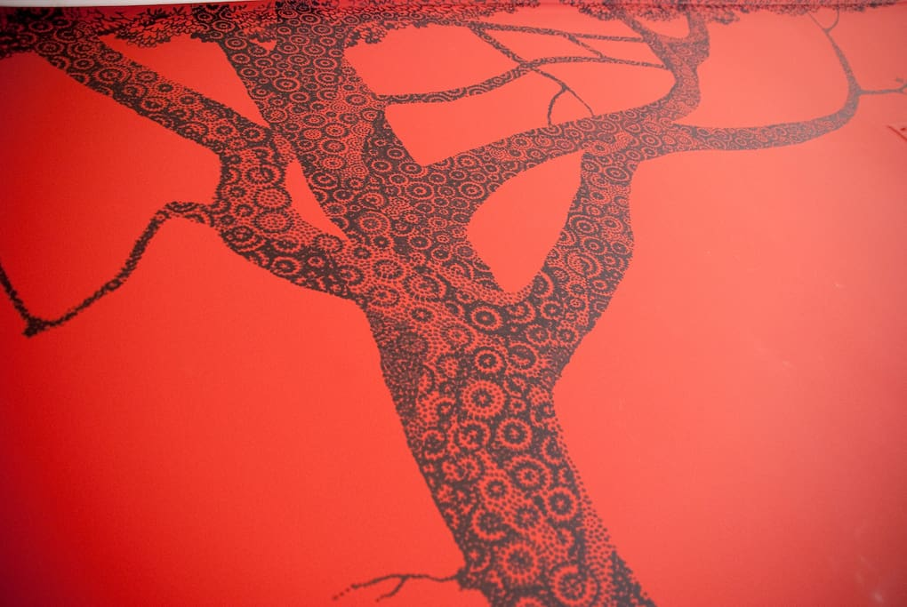 The tree mural behind the bed.