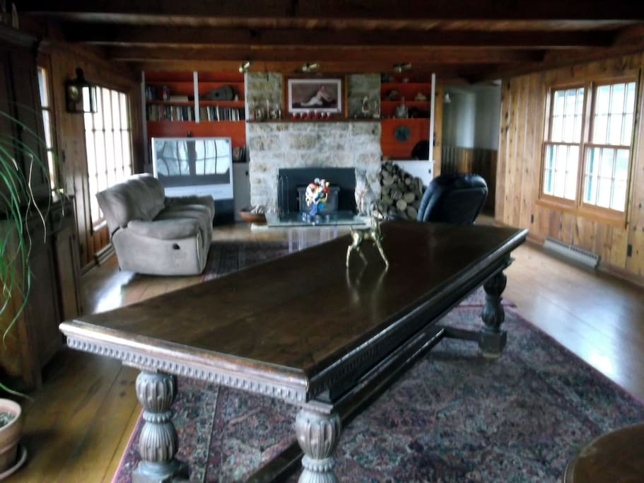The living room with large antique table and fireplace.