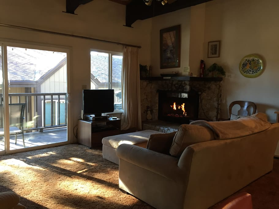 Spacious living room area with flat screen tv, fireplace and large balcony.