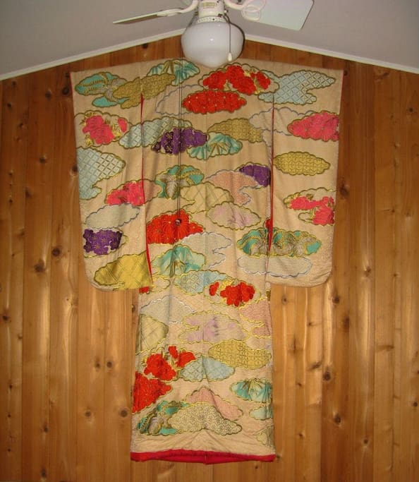 A Japanese wedding kimono hangs on the peaked wall of the living room, over the couch.