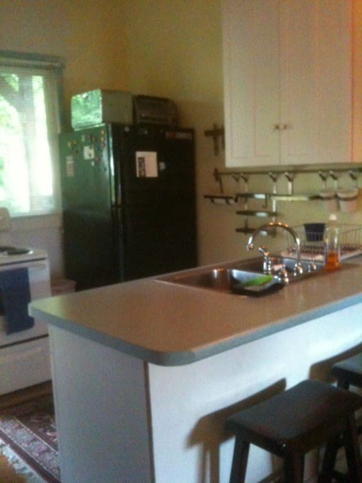 The kitchen with big fridge, stove, and counter top island with seating.