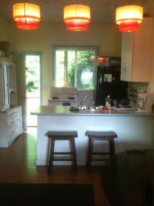 The kitchen with big fridge, stove, and countertop island with seating. (That's the back deck in the background.)