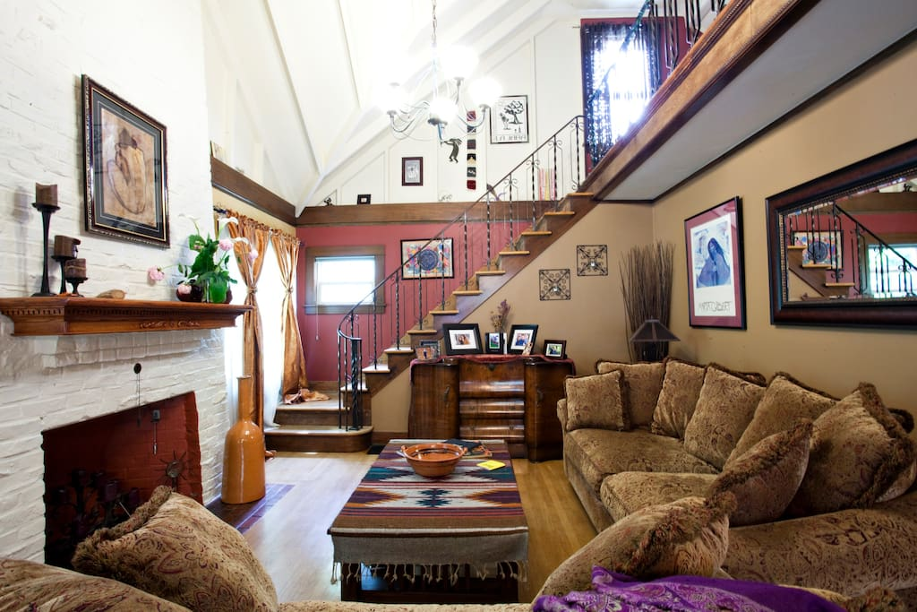 living room showing rod-iron staircase railing, very compy sofas