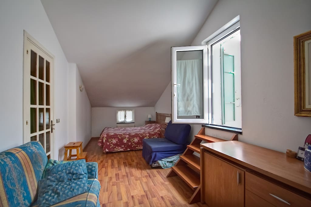 The room, you can see the double bed, the living room corner and the small stair che leads to the private terrace.
