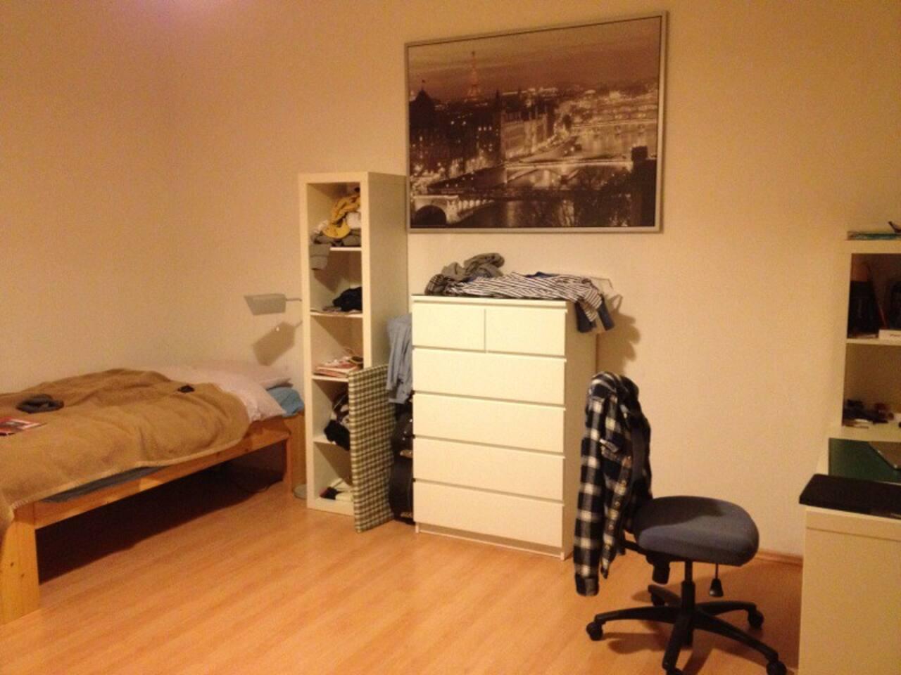 Dein 20qm Zimmer, mit Bett auf der linken Seite, Schränken, Schreibtisch rechts. Ein großes Fenster nach draußen.