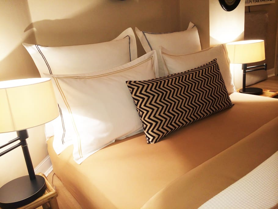 The bed in a wonderful Egyptian cotton 600 count thread bedding set from the Italian company Bellora in white,  caramel and black colors and handmade  stitching details, together with a long Ikat cushion and two brass swing arm lamps from Ralph Lauren Hom