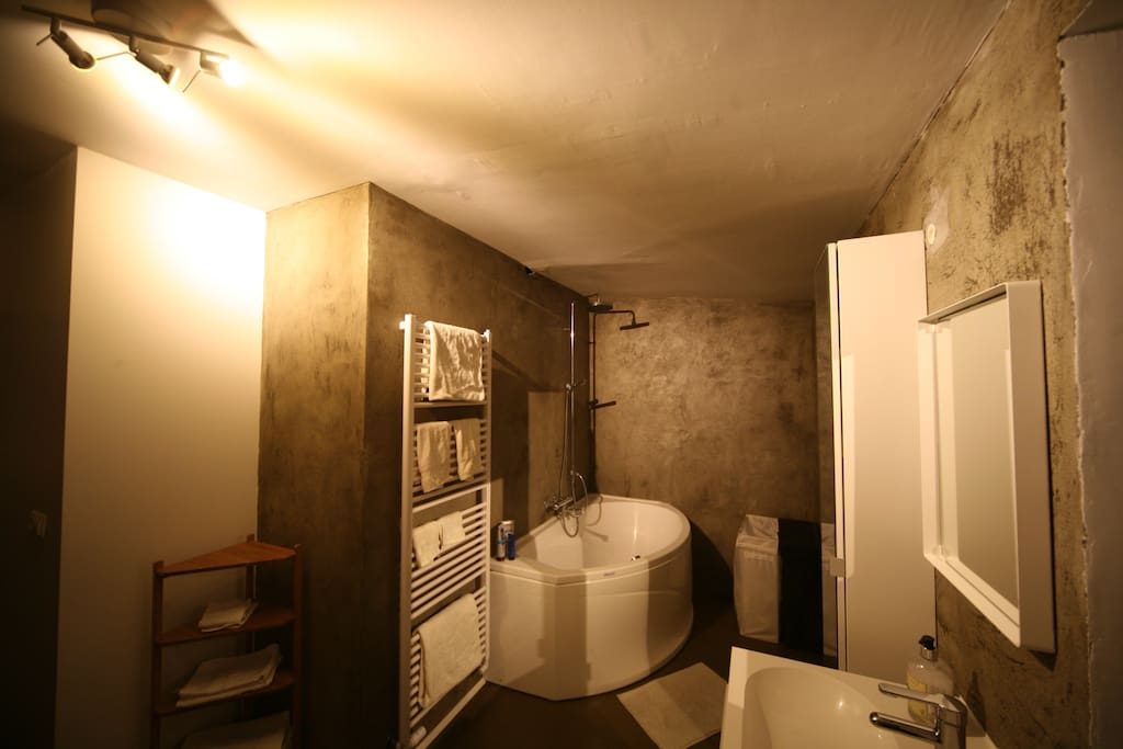 Very spacious bathroom with a large bathtub and floor heating