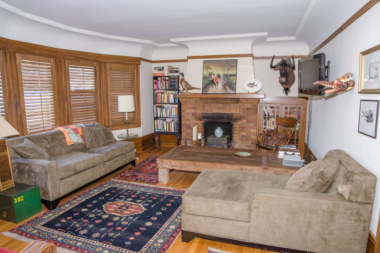 Living room with bay windows, fireplace, two large couches, and hardwood floors.