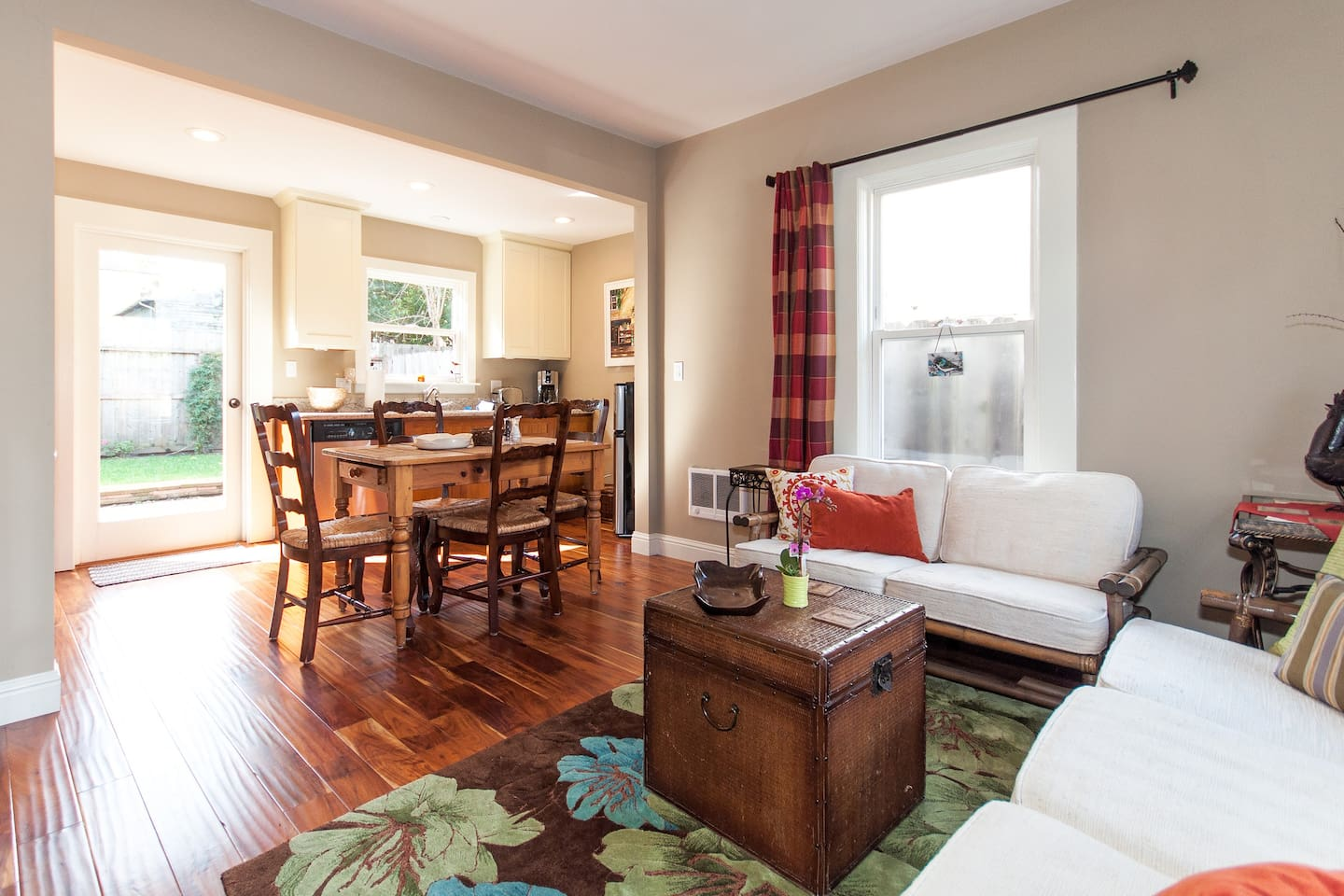 The living room area is open and bright with hardwood floors and plenty of comfortable seating.