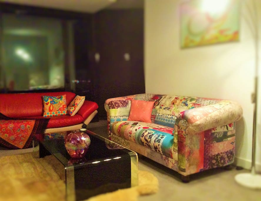 Cosy conversation nook, fun couch and red leather couch, black glass coffee table sheepskin rug